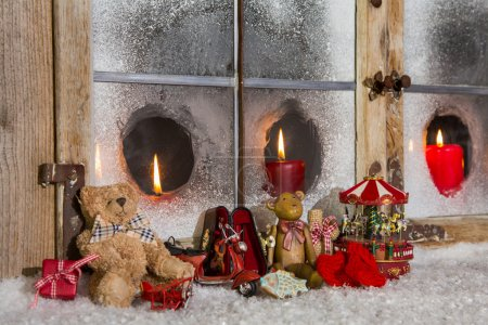 Christmas window decoration: candles with old children toys.