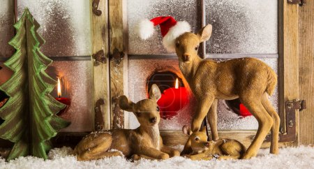 Christmas window decoration:  deer family with red candles.
