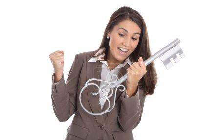 Photo pour Acclamations femme isolée contenant la clé de son premier appartement propre dans sa maison. - image libre de droit