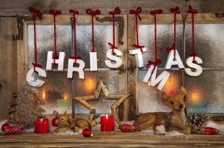 Outdoor christmas window decoration with red candles, deer and t