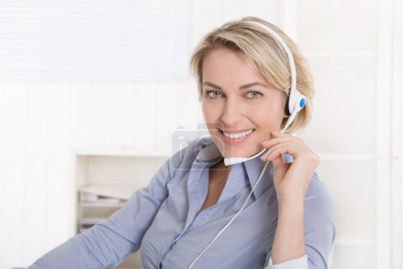 Attractive smiling middle aged woman in blue calling with headse