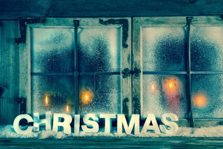 Atmospheric old christmas window with red candles and text.