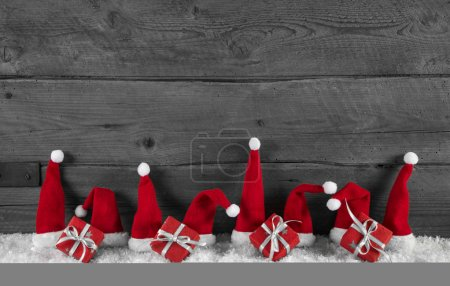 Wooden grey christmas background with red santa hats and gifts.