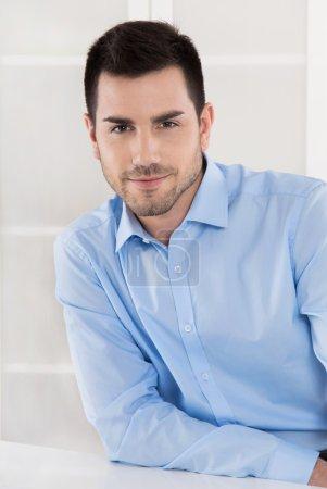 Photo pour Portrait : homme d'affaires prospère en chemise bleue assis dans son bureau . - image libre de droit
