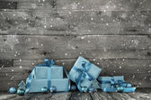 Grey wooden christmas background with a stack of presents in blu