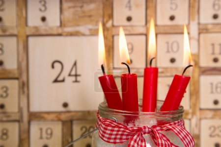 Four red burning advent candles with calendar.