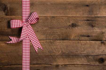 Wooden rustic background with a red white checkered ribbon.