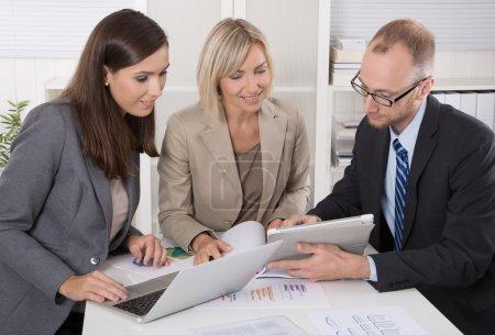 Photo pour Équipe de trois hommes d'affaires assis ensemble au bureau lors d'une réunion ou d'une discussion . - image libre de droit