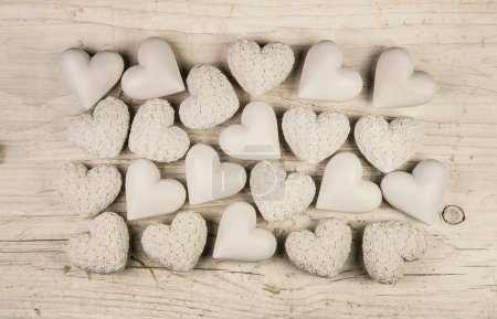 Photo for Beige or old white hearts on wooden shabby chic background for a greeting card. - Royalty Free Image