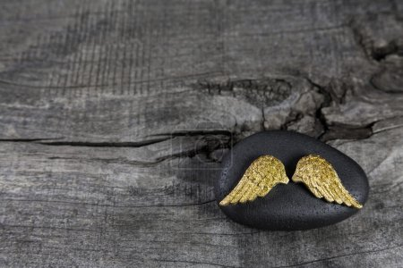 Golden angel wings on a black stone with grey wooden background.
