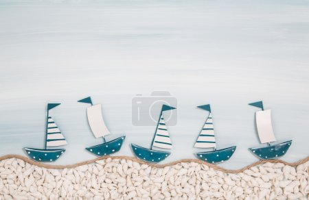 Five metal handmade sailboats on a blue ocean background for sum