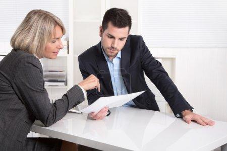 Successful teamwork: businessman and woman sitting at desk talki