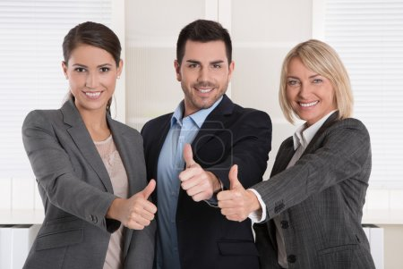 Thumbs up: three successful business people of man and woman in