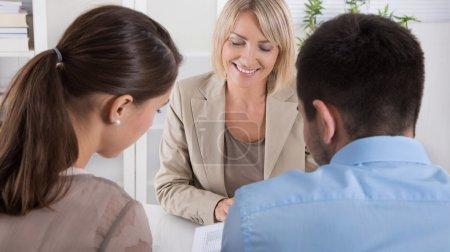 Photo pour Conseiller, courtier et clients assis au bureau. Jeunes couples qui planifient leur retraite . - image libre de droit