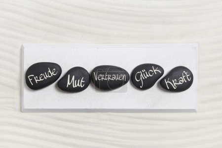 ive black stones with german text for happiness, courage, trust,