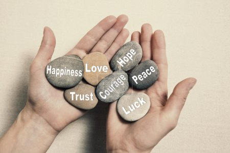 Photo pour Inner balance concept: hands holding stones with text for happiness, love, trust, courage, hope, peace and luck. - image libre de droit