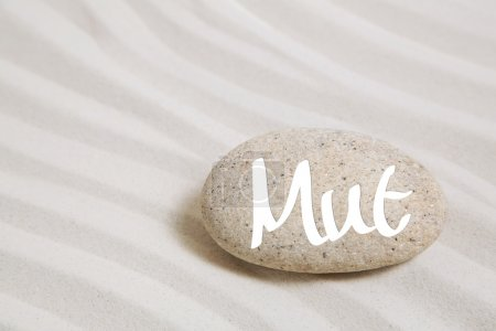 Sand background with a stone and the german word for courage.