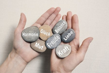 Photo pour Wellness concept with hands holding stones in german language: harmony, courage, luck, happiness, power and love. - image libre de droit