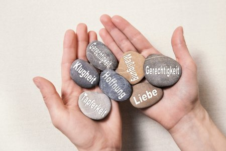 Inner balance concept: hands holding stones with german words fo