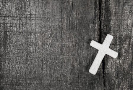 White cross on a grey wooden background.
