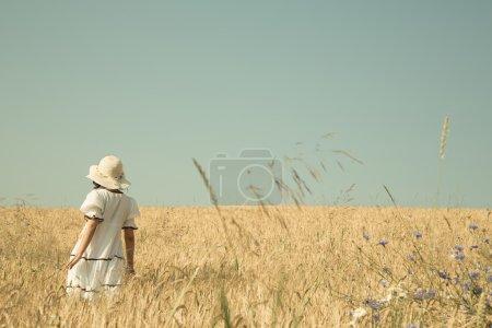 Summer dreams. Girl walking in a field of wheat with blue sky re