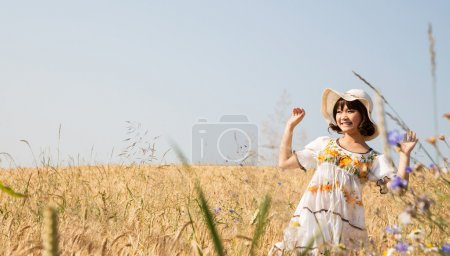 Photo for Happy cute girl in a wheat field with background. - Royalty Free Image
