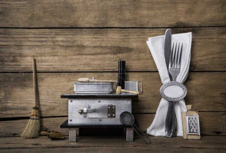 Old miniature of an oven with cutlery on an ancient rustic backg