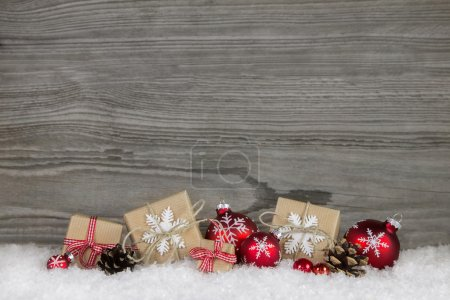 Regalos rojos de Navidad envueltos en papel natural sobre madera vieja gr