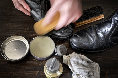 Photo for Shoes and polishing equipment on dark brown wooden surface - Royalty Free Image