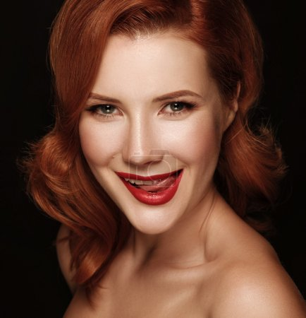 Close-up portrait of a smiling beautiful red-haired girl.