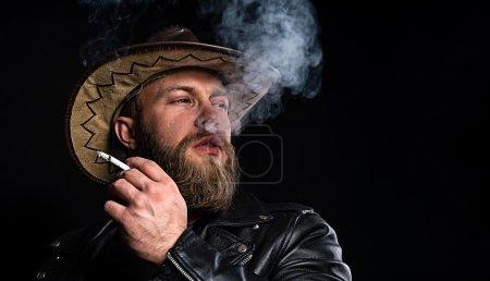 Photo pour Il fume une cigarette. Homme en chapeau de cow-boy avec une cigarette à la main sur fond noir . - image libre de droit