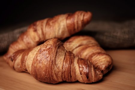 Photo for Some fresh croissants on a wooden surface. - Royalty Free Image