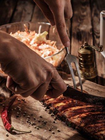 Photo pour Délicieuses côtes de barbecue avec salade de chou sur table en bois. Chef découper côtes de barbecue . - image libre de droit