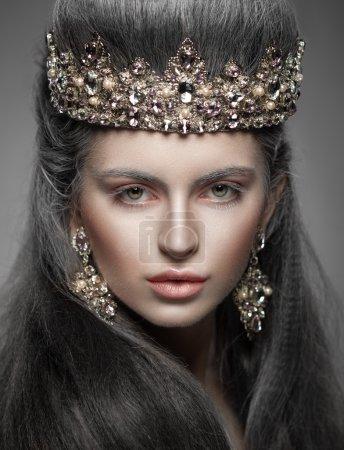 Photo pour Portrait d'une belle femme dans la Couronne de diamants et les boucles d'oreilles. Maquillage de fantaisie. Chignon. Cheveux longs. Regarder la caméra. - image libre de droit