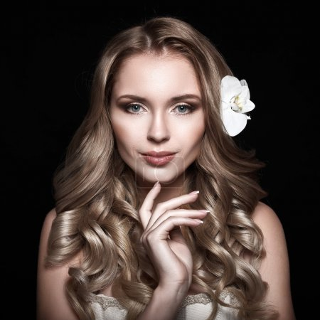 Photo for Beauty Girl. Smiling Beautiful blonde with long wavy hair. Flower in the hair. Evening make-up. Clean healthy skin. Beige background. Touching face. - Royalty Free Image
