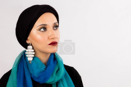Veiled Young Woman in high fashion dark make up and colorful scarf