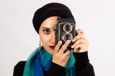 Young Woman holding old camera in hijab and colorful scarf