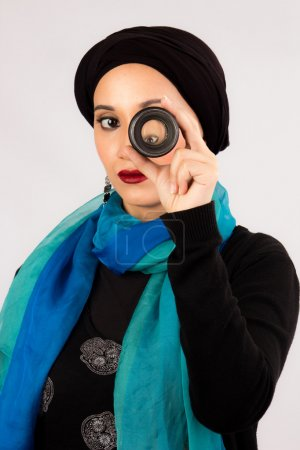 Young Woman holding a lens in hijab and colorful scarf