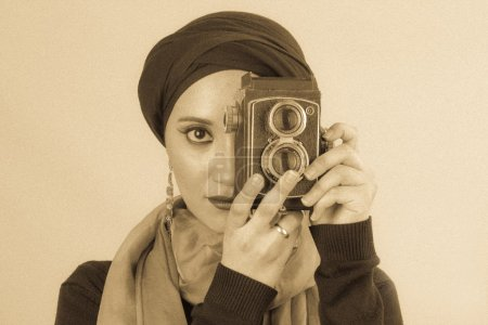 Young Woman holding old camera in hijab and scarf