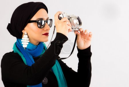 Young Woman holding old camera in hijab and colourful scarf