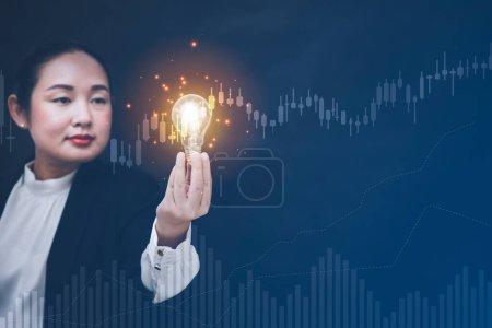 Photo pour Femme asiatique d'affaires tenant ampoule lumineuse avec innovation et créativité sont les clés du succès, l'innovation et l'inspiration, les idées et l'inspiration. concept - image libre de droit