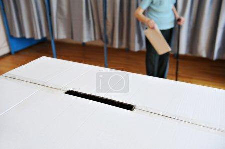 Photo pour Détail avec une urne et un vieillard en canne qui sort de la cabine de vote en arrière-plan - image libre de droit