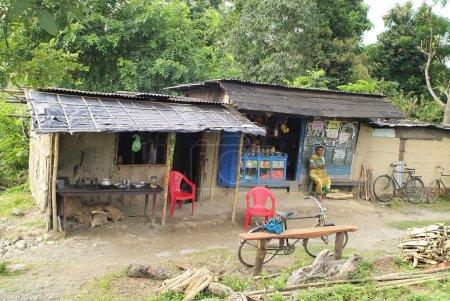 Photo pour Assam, Inde - 30 septembre 2007 : Femme indienne non identifiée devant un humble kiosque avec magasin général et petit restaurant, dans cette zone de l'Assam vivent beaucoup de pauvres sans aucune infrastructure - image libre de droit