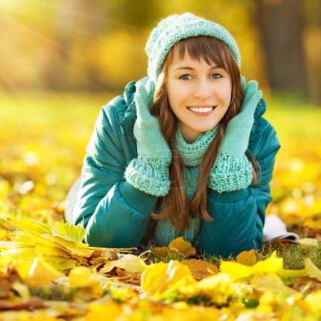 Photo pour Joyeux femme portant chapeau sarcelle lumineux et écharpe couché sur le sol parmi les arbres jaune vif dans le parc d'automne. Concept d'automne coloré . - image libre de droit