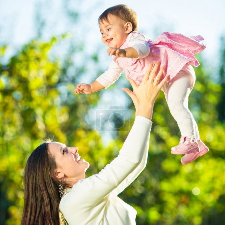 Photo pour La jeune mère et sa mignonne petite fille s'amusent dans le jardin ensoleillé. Joyeux concept d'enfance et de maternité . - image libre de droit