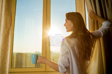 Woman holding cup of tea and looking at sunrise