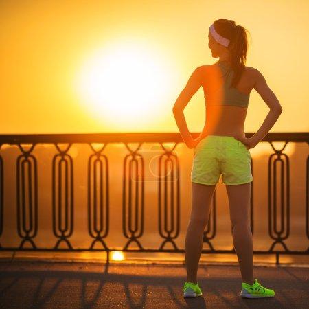Fitness woman watching sunrise on quay