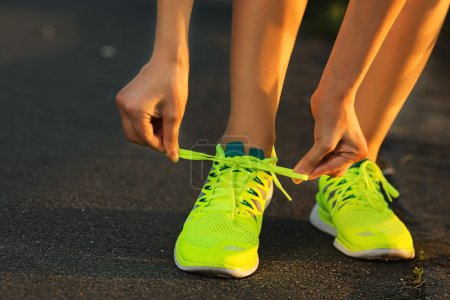 Woman tying laces on running shoes