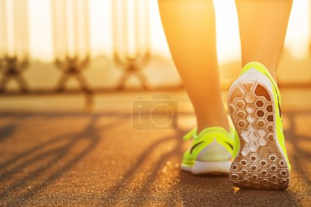 Photo for Runner woman feet running on road during sunrise, closeup on shoe. Sports healthy lifestyle concept. - Royalty Free Image