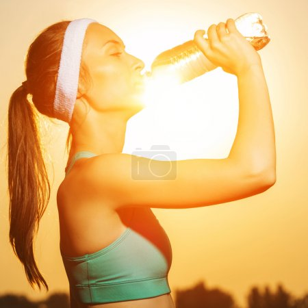 Photo pour Beautiful athletic woman drinking pure water from the bottle refreshing herself after running on a sunny bright light. Sports healthy lifestyle concept. - image libre de droit